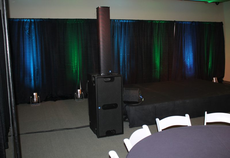 Two-Color uplighting makes for an interesting backdrop for an expo stage. Tech Works also provided the staging, drapery, audio and stage lighting.