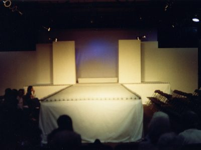A white colored carpeted runway stage and back walls with video screen, white skirting and belt lighting for a fashion show.