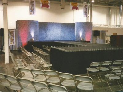 """A runway stage with front """"T"""" section, sponge painted back walls, black skirting, stage lighting and belt lighting for a JCPenney fashion show."""